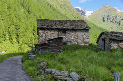Alpine stone shepherd's hut in a peasant village in the background of the Alps Royalty Free Stock Photos