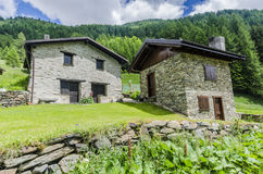 Alpine stone shepherd's hut in a peasant village in the background of the Alps Royalty Free Stock Image