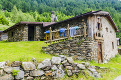 Alpine stone shepherd's hut in a peasant village in the background of the Alps Stock Photos