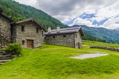 Alpine stone shepherd's hut in a peasant village in the background of the Alps Stock Photo