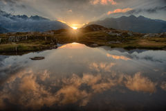 Alpine Sunrise. In Switzerland with reflected clouds in the pond Royalty Free Stock Photography