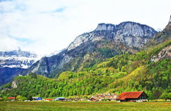 Alpine Switzerland landscape. Village on green spring valley on the foot of Alps mountains, Switzerland royalty free stock photo