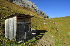 Alpine toilet. A small wooden outhouse standing isolated hight in the Swiss alps Stock Photos