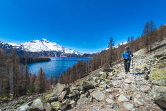 Alpine trekking on the Swiss Alps a girl hiking with a large lak Stock Photos