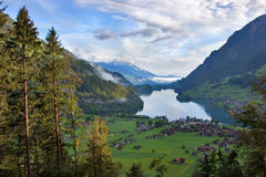 The Alpine valley. Wonderful lake in the Swiss Alpes and village on coast Royalty Free Stock Photography
