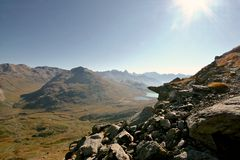 Alpine valley seen from a rocky ridge. Hiking in Swiss Alps. Royalty Free Stock Images