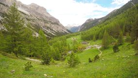 Alpine valley view from the top in summer time. With lush green landscape of pasture, meadows and larch tree forest stock footage