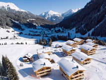Alpine village. Gargellen, a village in the Austrian Alps, with snow covered chalets in the foreground and mountains in the background Royalty Free Stock Image