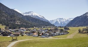 Alpine village in the Austrian Alps - Stock Photo. A Alpine village in the Austrian Alps with snowy mountains in the background Royalty Free Stock Images