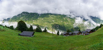 Alpine village in foggy clouds Stock Image