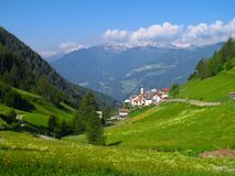 Alpine village in Italian Alps valley mountains spring summer. Alpine village of Planeil, Italy nestles in a green valley on a sunny blue sky day as the Alps Stock Photography