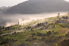Alpine village in mountains. Smoke, bonfire and haze over hills Royalty Free Stock Photography