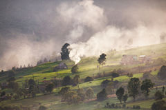 Alpine village in mountains. Smoke, bonfire and haze over hills Stock Photo