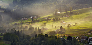 Alpine village in mountains. Smoke and haze over hills Royalty Free Stock Photos