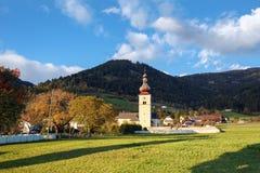 Alpine village Obermillstatt, Gurktal Alps, Austria. St. John Church in the fall. Alpine village Obermillstatt, Gurktal Alps & x28;Nock Mountains& x29;, state of Royalty Free Stock Photos