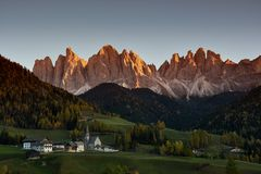 Sunset on The Alpine Village of Santa Magdalena in Val di Funes with the dolomitic group of the Odle on the background. The Alpine Village of Santa Magdalena in Stock Images