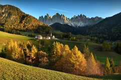 Sunset on The Alpine Village of Santa Magdalena in Val di Funes with the dolomitic group of the Odle on the background. The Alpine Village of Santa Magdalena in Royalty Free Stock Images