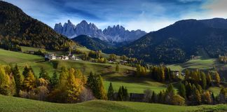 The Alpine Village of Santa Magdalena in Val di Funes with the dolomitic group of the Odle on the background. The Alpine Village of Santa Magdalena in Val di Royalty Free Stock Photography