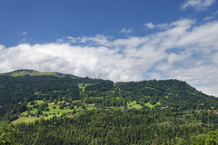 Alpine village on slope of hill panoramic landscape Stock Photos