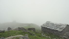 Alpine village on slope of Himalaya mountain in mist. Mountain village on slope of Himalaya mountain, silhouette of cows grazing on green alpine pasture in misty stock video footage