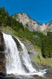 Alpine waterfall in mountain forest. With rainbow under blue sky Royalty Free Stock Image