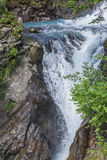 Alpine waterfall in mountain forest. With big rock faces stock images