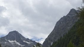 Alpine weather time lapse. Clouds forming and piling up behind a tall mountain ridge, gathering strength stock video