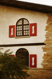 Alpine Windows. Alpine cottage in the summer. Warm inviting building Stock Image