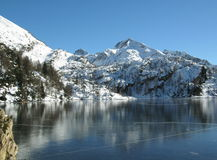 Alpine winter Landscape. Frozen lake in a winter mountain landscape - Italian Alps Royalty Free Stock Image
