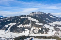 Alpine winter landscape peak with snow, forest and clouds stock photo
