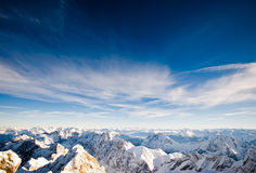 Alpine winter mountaintop view. A high altitude view overlooking snow-capped mountains from the Zugspitze mountain in the Tirolean Alps Royalty Free Stock Photo