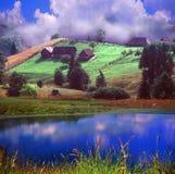 Alpiner Bauernhof umgeben durch den Fluss Lizenzfreie Stockbilder