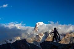 Alpiner Bergsteiger, der Gipfel erreicht Stockfotografie