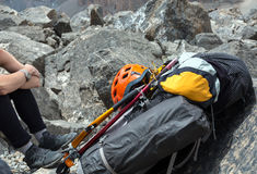 Alpiner Rucksack mit dem kletternden Gang befestigt Lizenzfreie Stockbilder
