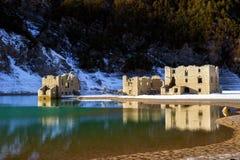 Alpiner See mit Ruinen von alten Häusern versenkte teilweise durch Wasser Lizenzfreies Stockbild