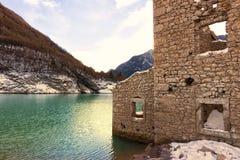 Alpiner See mit Ruinen von den alten Häusern teilweise versenkt Stockfotografie