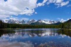 Alpiner See, Schnee bedeckte Berge, Wolken und Reflexionen mit einer Kappe Lizenzfreies Stockfoto