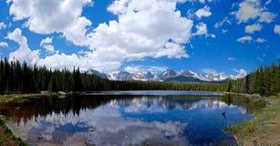 Alpiner See, Schnee bedeckte Berge, Wolken und Reflexionen mit einer Kappe Lizenzfreie Stockfotos