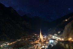 Alpines Dorf nachts mit Bergen und sternenklarem Himmel Stockfoto
