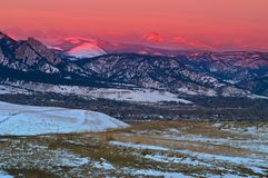 Alpinglow snow mountains at sunrise over Boulder stock photos
