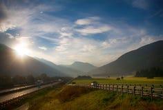 Alpinian väg med bilar på soluppgång Royaltyfri Bild