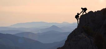 Alpinisme d'aide et représentation de crête photo stock