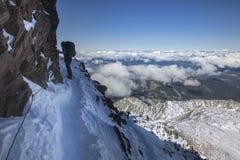 Alpinismo che sale alla cima sopra le nuvole in alpi francesi Fotografie Stock Libere da Diritti