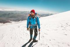 Alpinismo dello scalatore dell'uomo con la piccozza da ghiaccio in montagne Fotografie Stock
