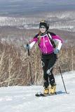 Alpinismo dello sci, corsa verticale: l'alpinista sorridente dello sci della ragazza scala sugli sci sulla montagna Fotografie Stock Libere da Diritti