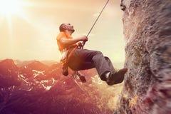 Alpinismo do homem uma cara precipitado da rocha Foto de Stock Royalty Free