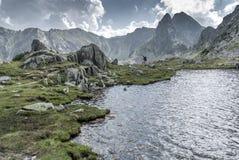 Alpinismo por el lago de la montaña entre picos y nubes rocosos Imagenes de archivo