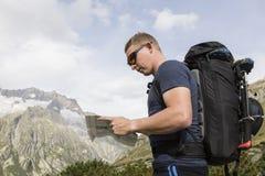 Alpinist ориентирован с картой на местности Стоковое Изображение