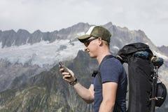 Alpinist ориентирован с прибором GPS в местности Стоковые Изображения