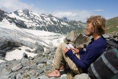alpinist смотря горы карты к одичалому Стоковое Изображение RF